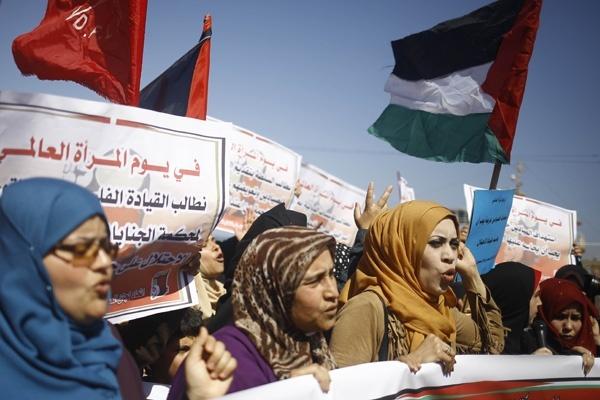 Perempuan Palestina memegang bendera nasional saat berdemonstrasi di Gaza City dalam memperingati Hari Perempuan Internasional pada 9 Maret 2017. Mohammed Abed/AFP